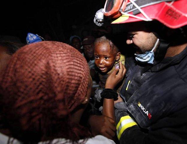 Haiti, dwuletni Redjeson Hausteen Claude oddawany matce po tym jak belgijsko-hiszpańska ekipa ratunkowa wydostała go spod gruzów - fot. Gerald Herbert AP